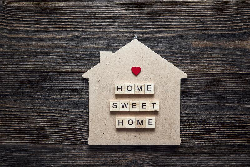 Home symbol with quote and heart shape on wooden background. royalty free stock photos