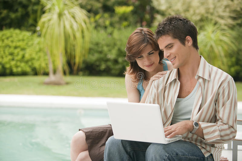 Home Tech Couple with Laptop by Pool royalty free stock photo