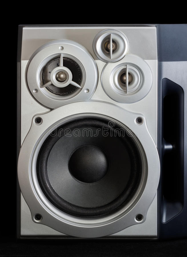 Home three-way loudspeaker system on a dark background. Fragment of home high fidelity three-way loudspeaker system with bass reflex port in silvery housing on a royalty free stock images