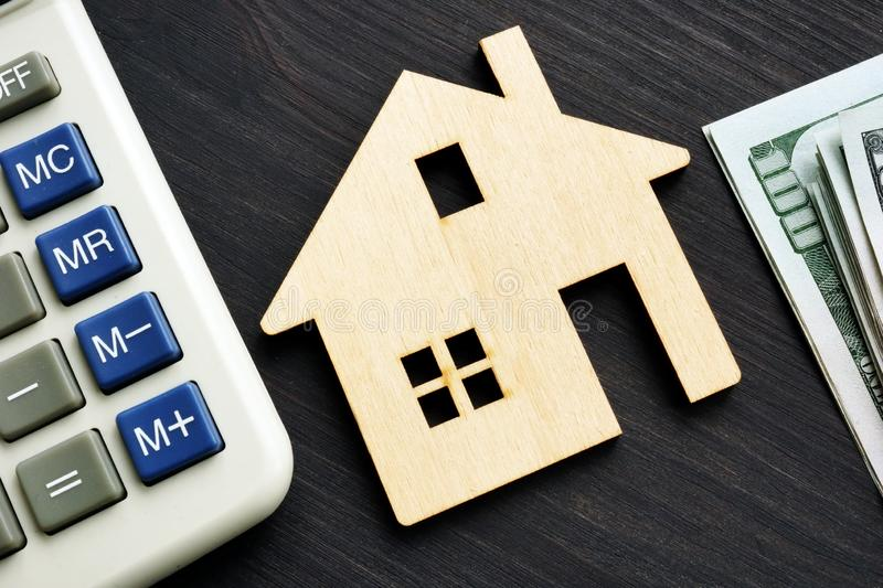 Home value. Wooden house with calculator stock image