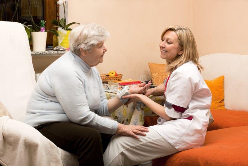Home visit nurse with senior. Nurse makes home visit and measures blood pressure stock images