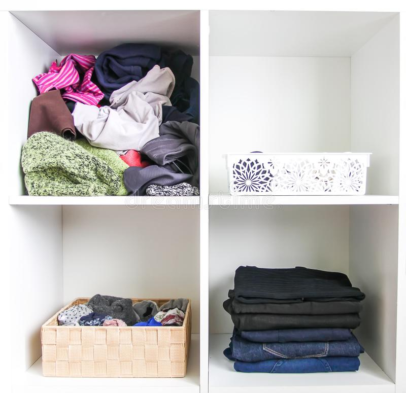 Home wardrobe with different clothes. Small space organization. The contrast of order and disorder stock images