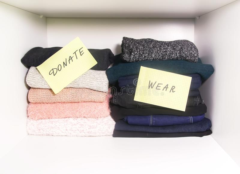 Home wardrobe with different items of clothing. Seasonal clothes sorting. Small space organization stock photography