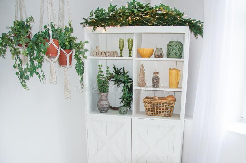 home winter christmas design of interior of kitchen wooden white cupboard with words dream,plants ,yellow and green decorations stock image