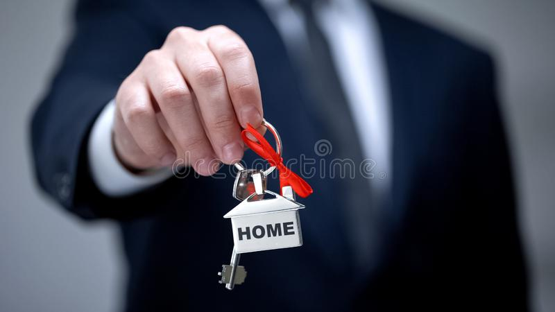 Home word on keychain in businessman hand, house purchase, rental services. Stock photo royalty free stock image
