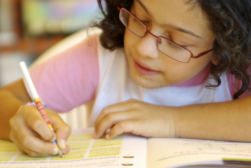 Home-Work. Concentrated young girl doing her school home-work royalty free stock photos