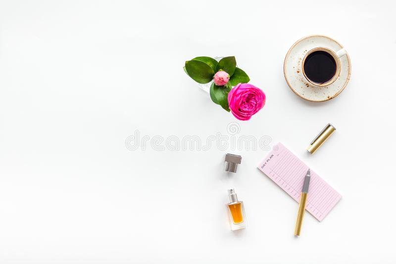 Home work desk, feminine workplace. Notebook and stationery near pink flowers and coffee on white background top view stock photography