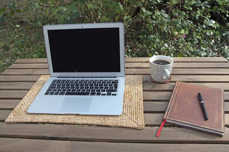 Home working in garden with laptop. Working from home with laptop, coffee and notebook in garden royalty free stock photo