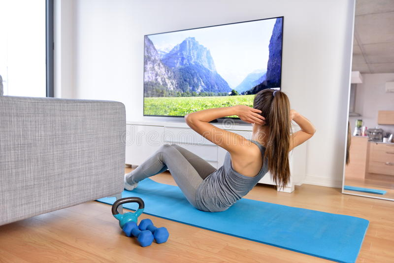 Home workout - woman exercising in front of TV stock photos