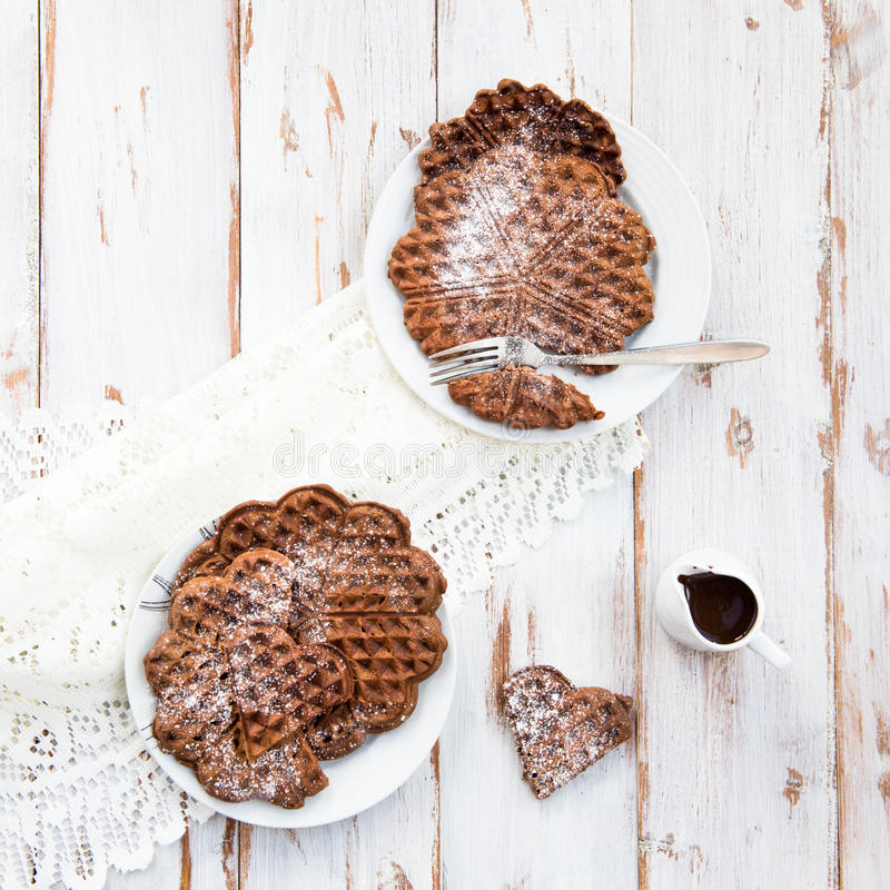 Homebaked Chocolate Waffles. Homebaked Chocolate Heart Shaped Waffles with Melted Hot Chocolate on White Plate, Top View stock photo