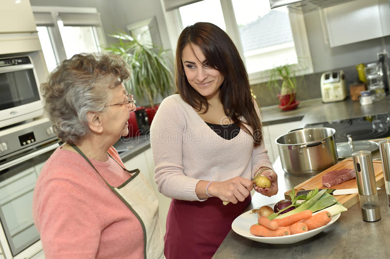 Homecare assistant helps cooking for an elderly woman stock photo