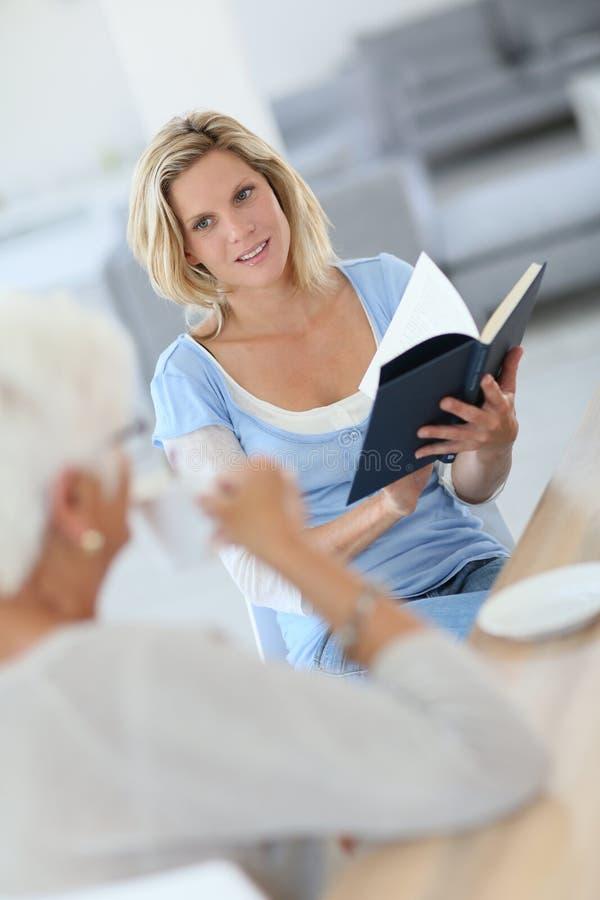 Homecarer läs- berättelse till åldring royaltyfria bilder