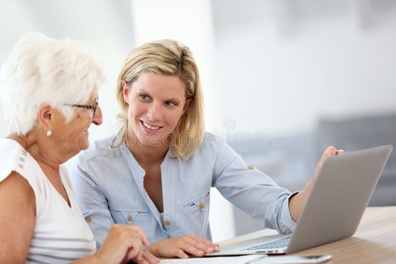 Homecarer och äldre dam som använder bärbara datorn arkivbilder