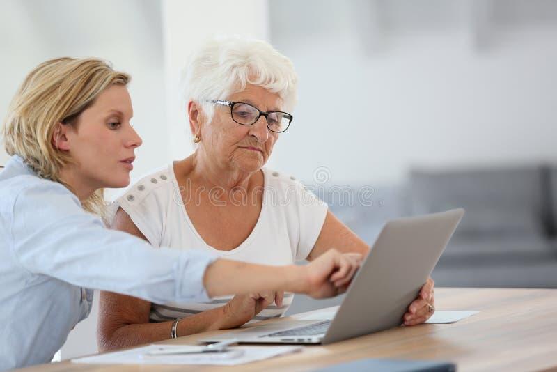 Homecarer som förklarar till den höga kvinnan hur man använder bärbara datorn royaltyfri foto