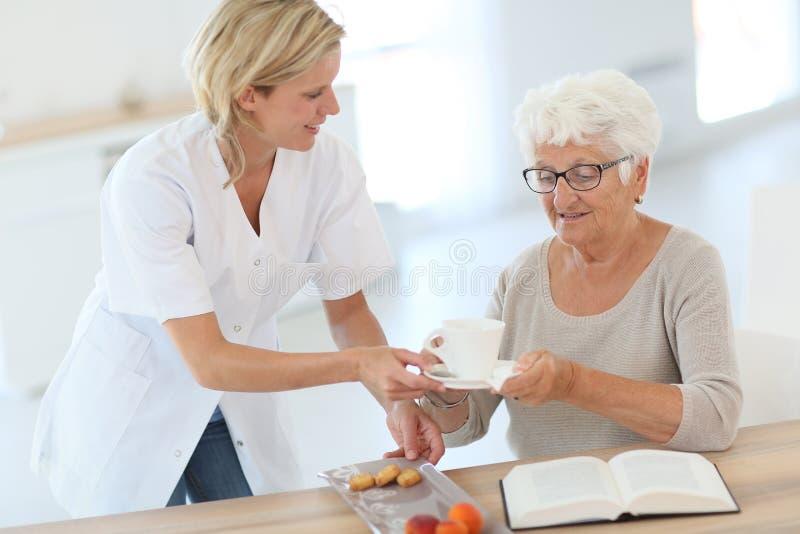 Homecarer som kommer med te till den äldre kvinnan royaltyfri fotografi
