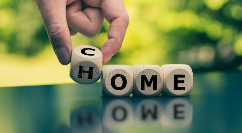 Homecoming concept. Hand turns a cube and changes the word. `come` to `home royalty free stock image