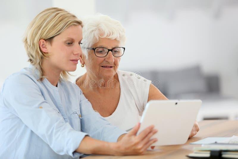 Homehelper med den äldre kvinnan som använder minnestavlan arkivbild