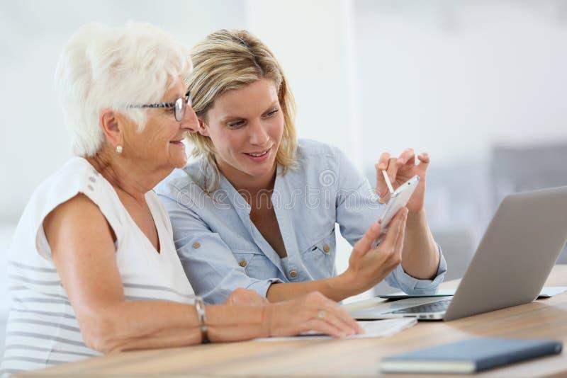 Homehelper met bejaarden die elektronische apparaten met behulp van stock afbeelding