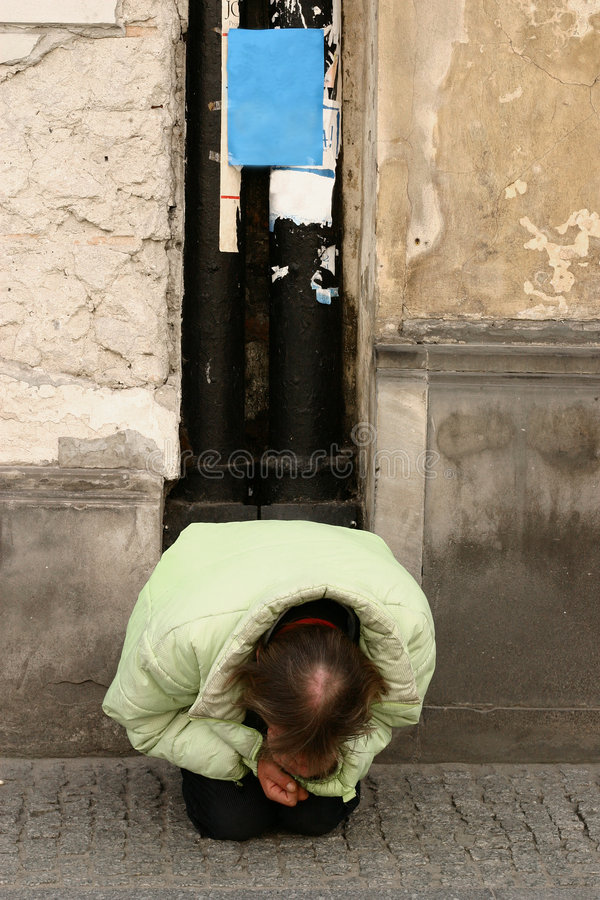 Homeless. Man begging on a sidewalk royalty free stock image