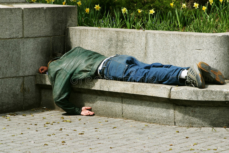 Homeless. Man sleeping on a bench stock photography