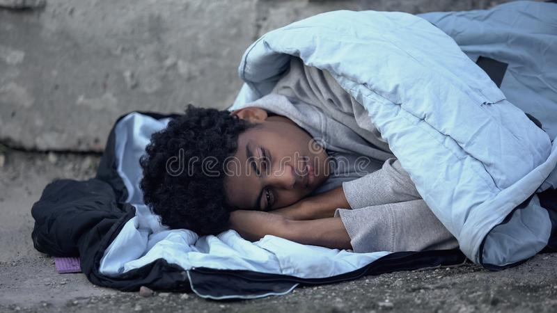 Homeless african teenager lying in sleeping bag ground, poverty unemployment stock image