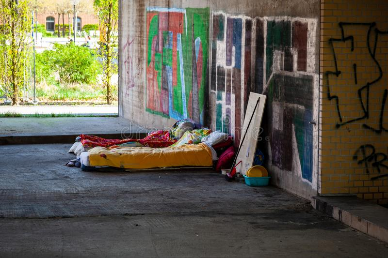 Homeless beds in spring in urban setting. Beds bedding and possessions of homeless people in an underpass in Berlin in early spring stock photos