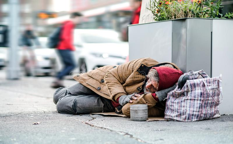 Homeless beggar man lying on the ground outdoors in city asking for money donation. royalty free stock photos