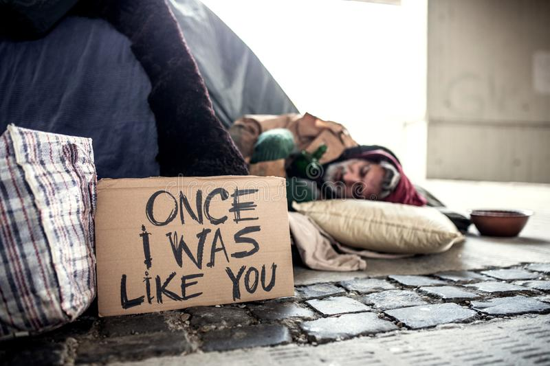 Homeless beggar man lying on the ground outdoors in city, sleeping. royalty free stock images