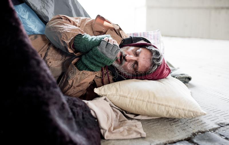Homeless beggar man lying on the ground outdoors in city, warming up hands. stock photography
