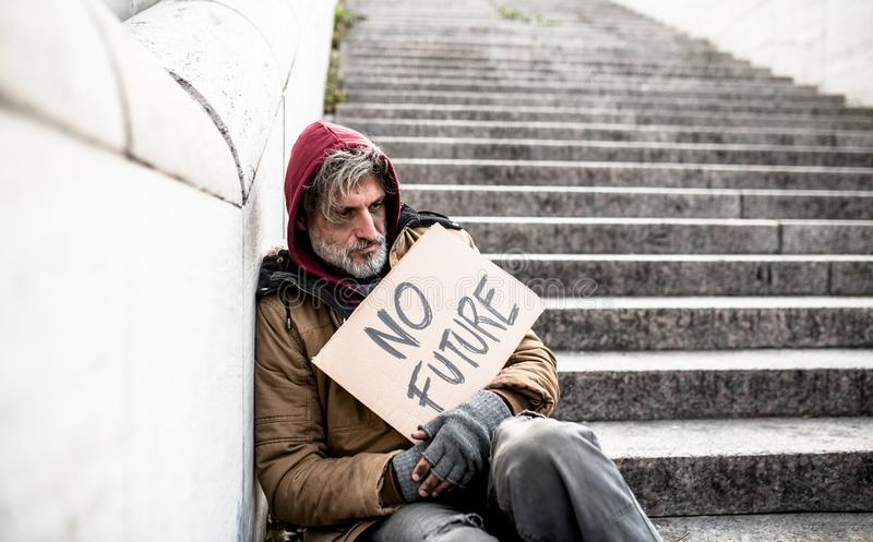 Homeless beggar man sitting outdoors in city holding no future cardboard sign. stock images