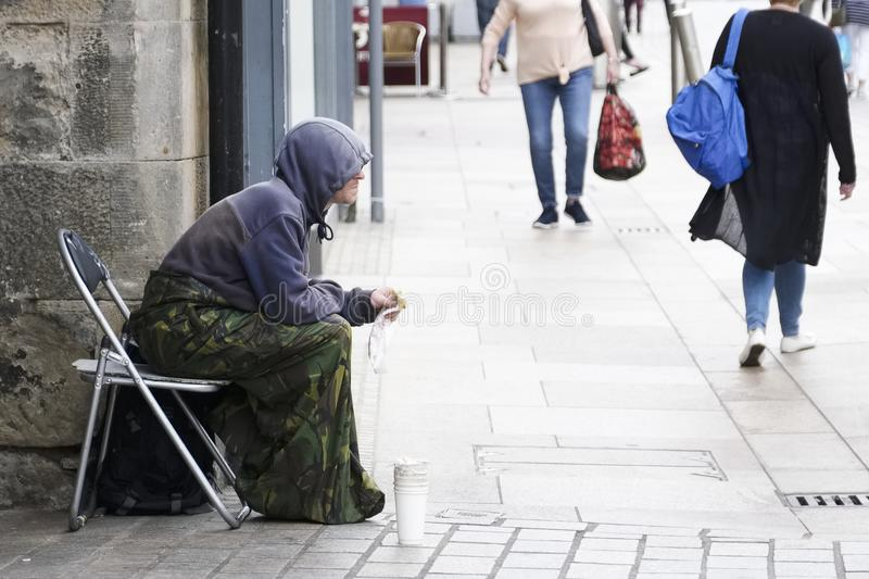 Homeless beggar sat on busy street wearing a hoodie with cup for change in the UK with shoppers in the background stock images