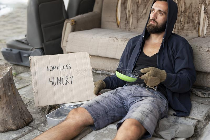 Homeless beggar in the street. Beggar wearing hoodie over cap and fingerless gloves, sitting in the street, begging for money royalty free stock photo