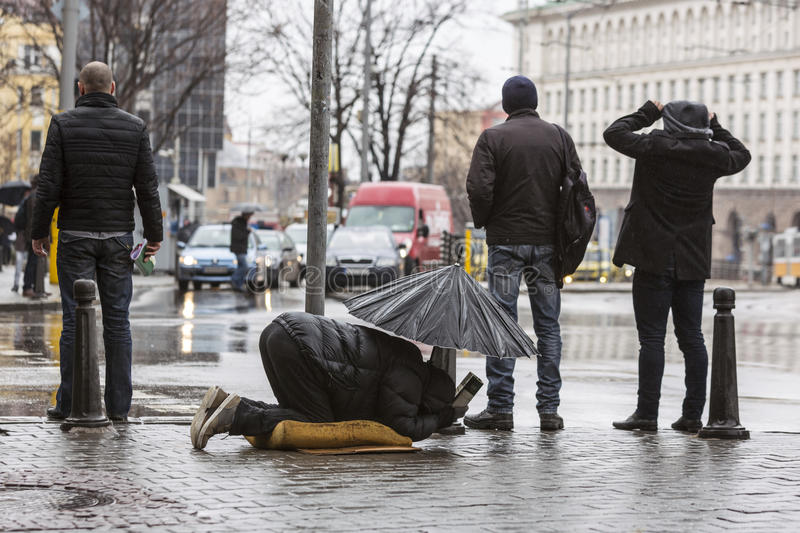 Homeless beggar with umbrella in the rain royalty free stock photo