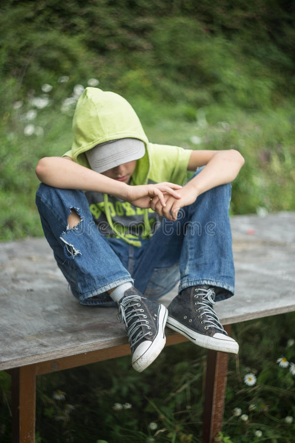 A homeless boy sits on a bench with her head bowed down stock photos