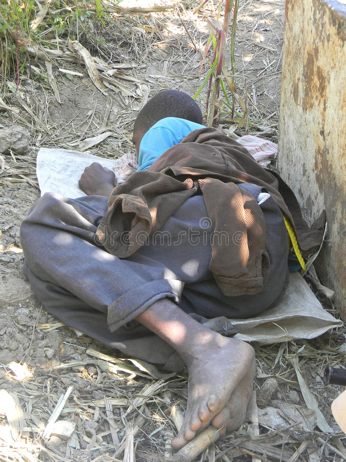 Homeless boy sleeping under a tree. Harare,Zimbabwe.April 27 2015. A barefooted homeless boy sleeping under a tree.Rapid urbanization has increased homelessness royalty free stock images