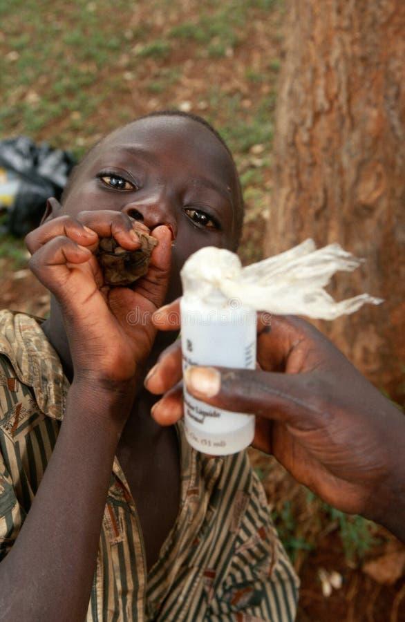 A homeless boy sniffing glue in Kampala, Uganda royalty free stock photo