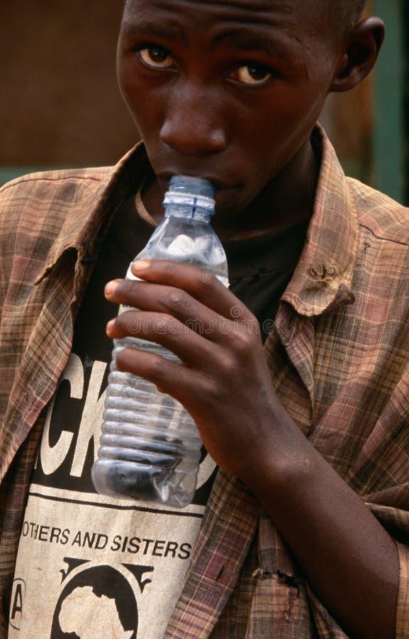 A homeless boy sniffing glue in Kampala, Uganda royalty free stock image