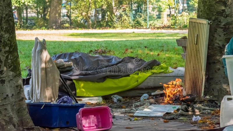 Homeless camp in the park. With a bonfire stock image