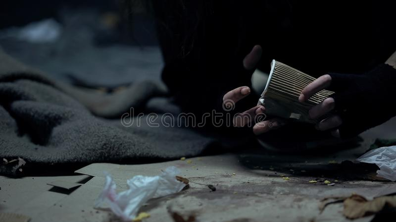 Homeless dirty woman holding beggar cup in dark place, social problems, charity royalty free stock photos