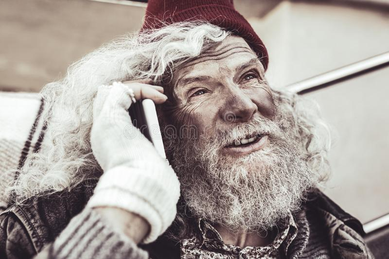 Homeless elderly looking at people and describing them to friend on the phone. stock image
