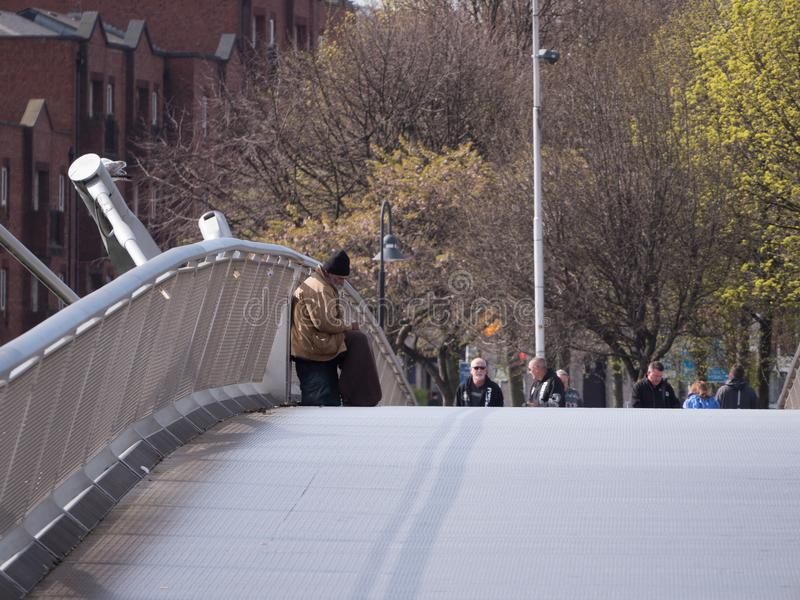 Homeless elderly man sitting begging on the Millennium Bridge in Dublin Ireland. As people walk by on a winter day stock photo