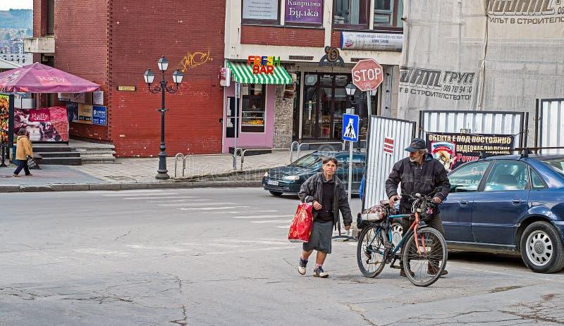 Homeless family with bike. Veliko Tarnovo city, Bulgaria - March 27, 2017. Homeless family with bike stock photography