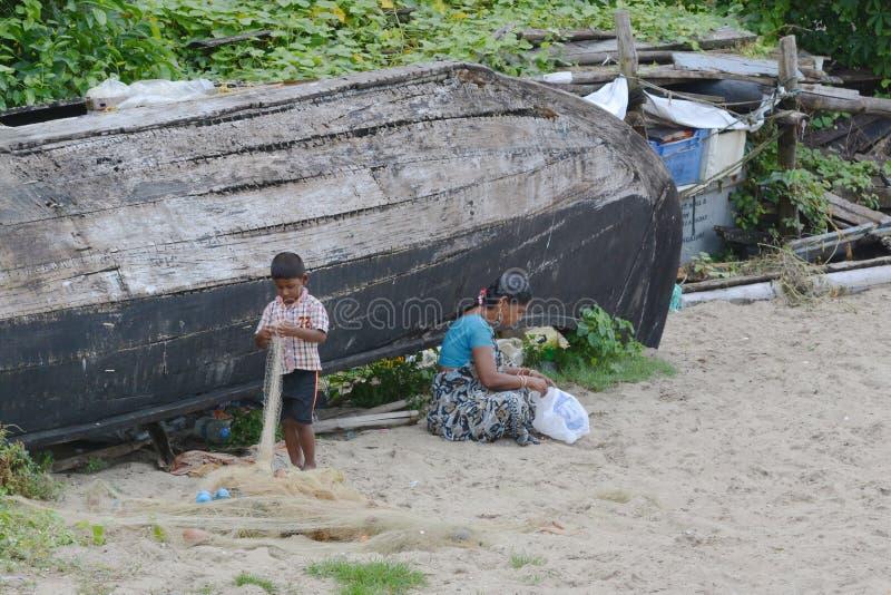 Homeless family in India. Kochi, India - November 1, 2015 - Homeless family sitting near boat on beach of Kochi, India royalty free stock images