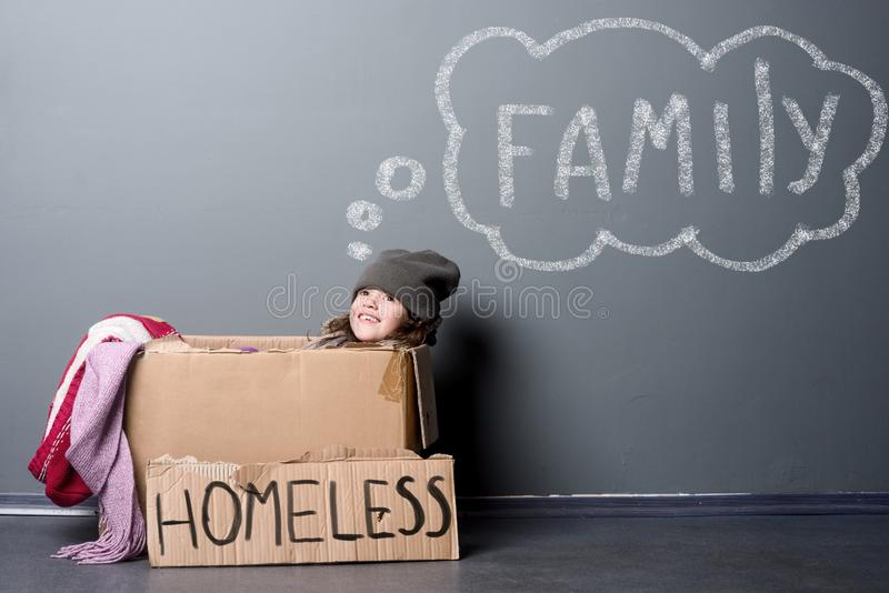 Homeless girl in paper box. Smiling girl sitting in a paper box, sign Homeless. Second-hand clothes, grey background. Dreaming about a family royalty free stock photo