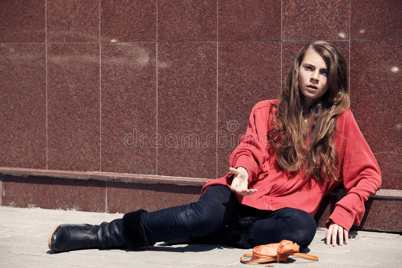 Homeless girl. Sitting on the floor royalty free stock image