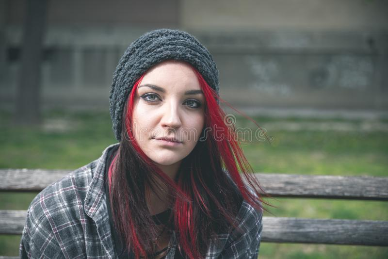 Homeless girl, Young beautiful red hair girl sitting alone outdoors on the wooden bench with hat and shirt feeling anxious. Young beautiful red hair girl sitting royalty free stock images