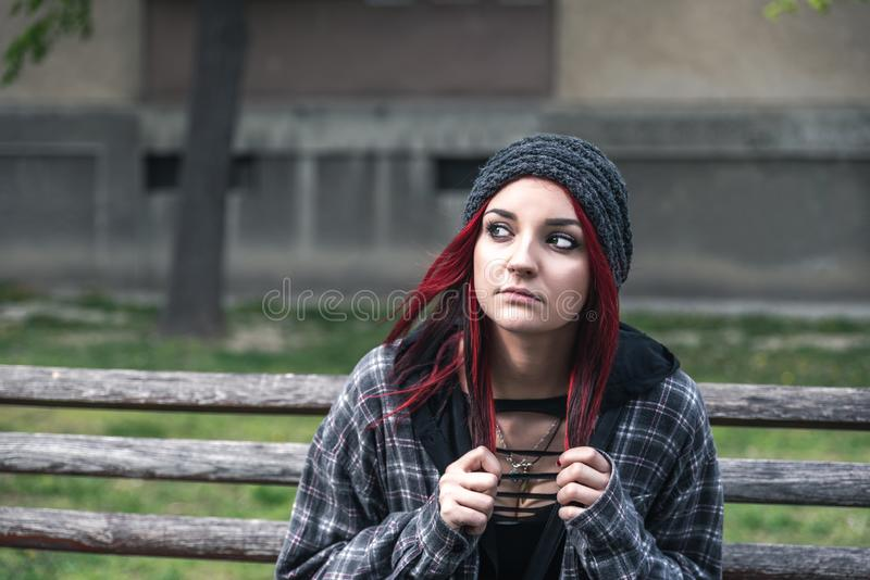 Homeless girl, Young beautiful red hair girl sitting alone outdoors on the wooden bench with hat and shirt feeling anxious. Young beautiful red hair girl sitting stock photos