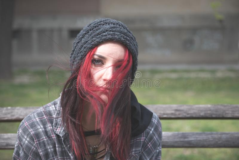 Homeless girl, Young red hair girl sitting alone outdoors with hat and shirt anxious and depressed after she became a homeless. Young beautiful red hair girl stock photo