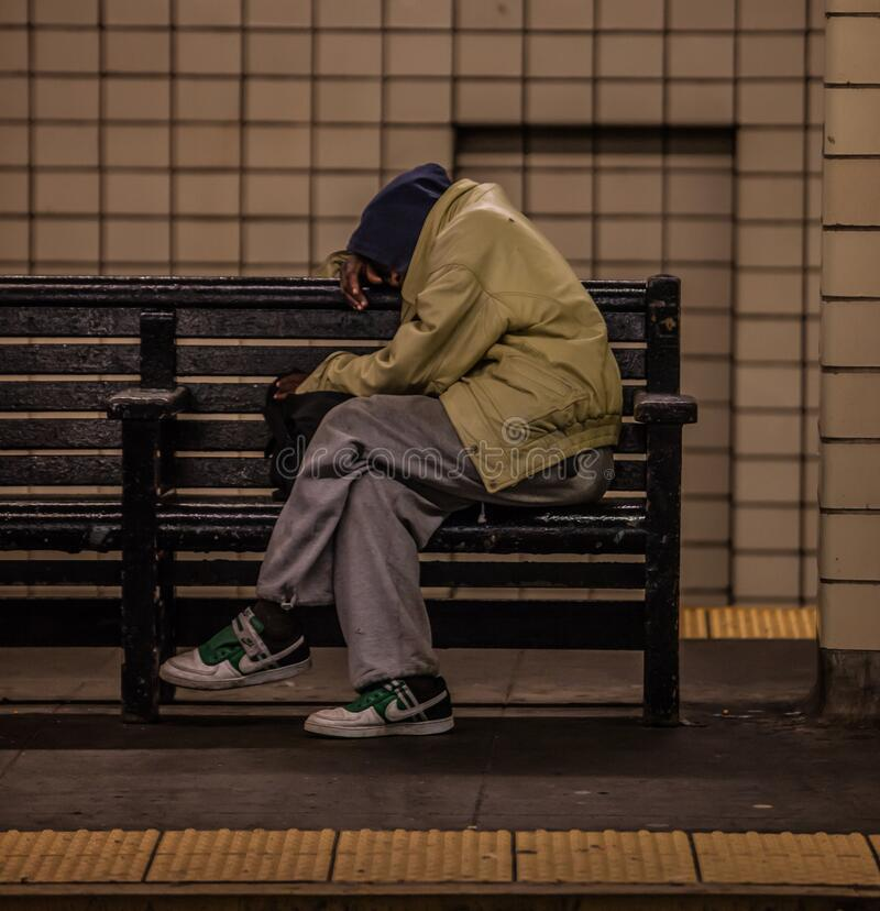 A homeless guy asleep in a subway station in New York. New York, United States - September 21 2009 : a homeless person is asleep on a bench on the subway stock image