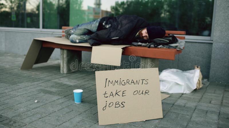 Homeless and jobless european man with cardboard sign sleep on bench at city street because of immigrants crisis in royalty free stock image